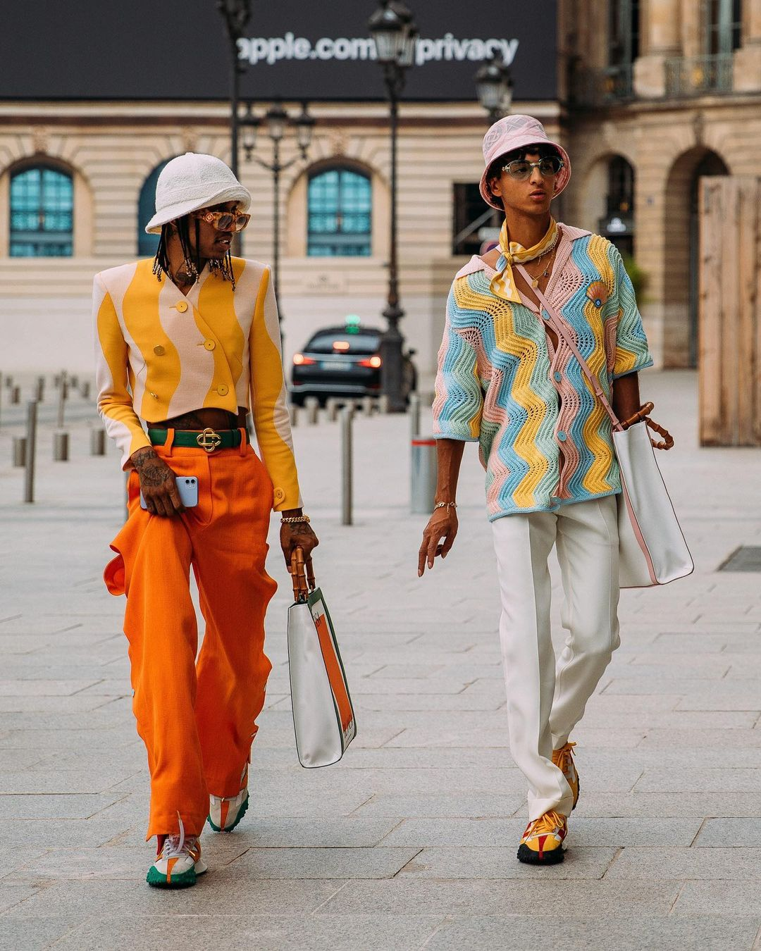 Two men walking in the street wearing bright shirts and hats