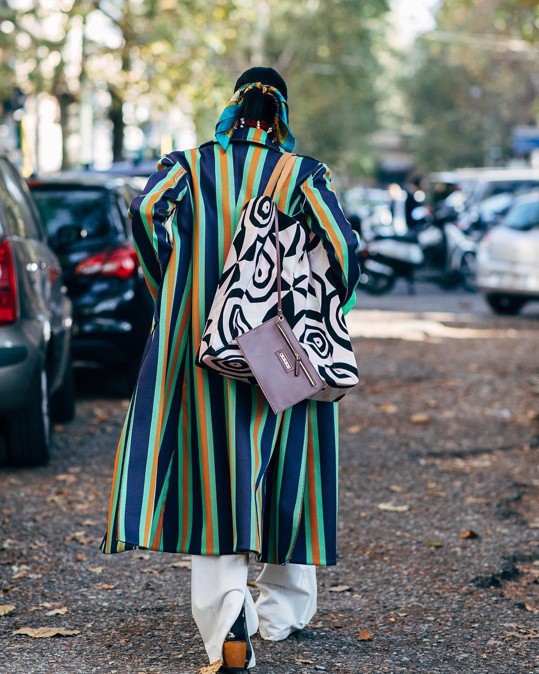 Women walking down the street in a long striped coat