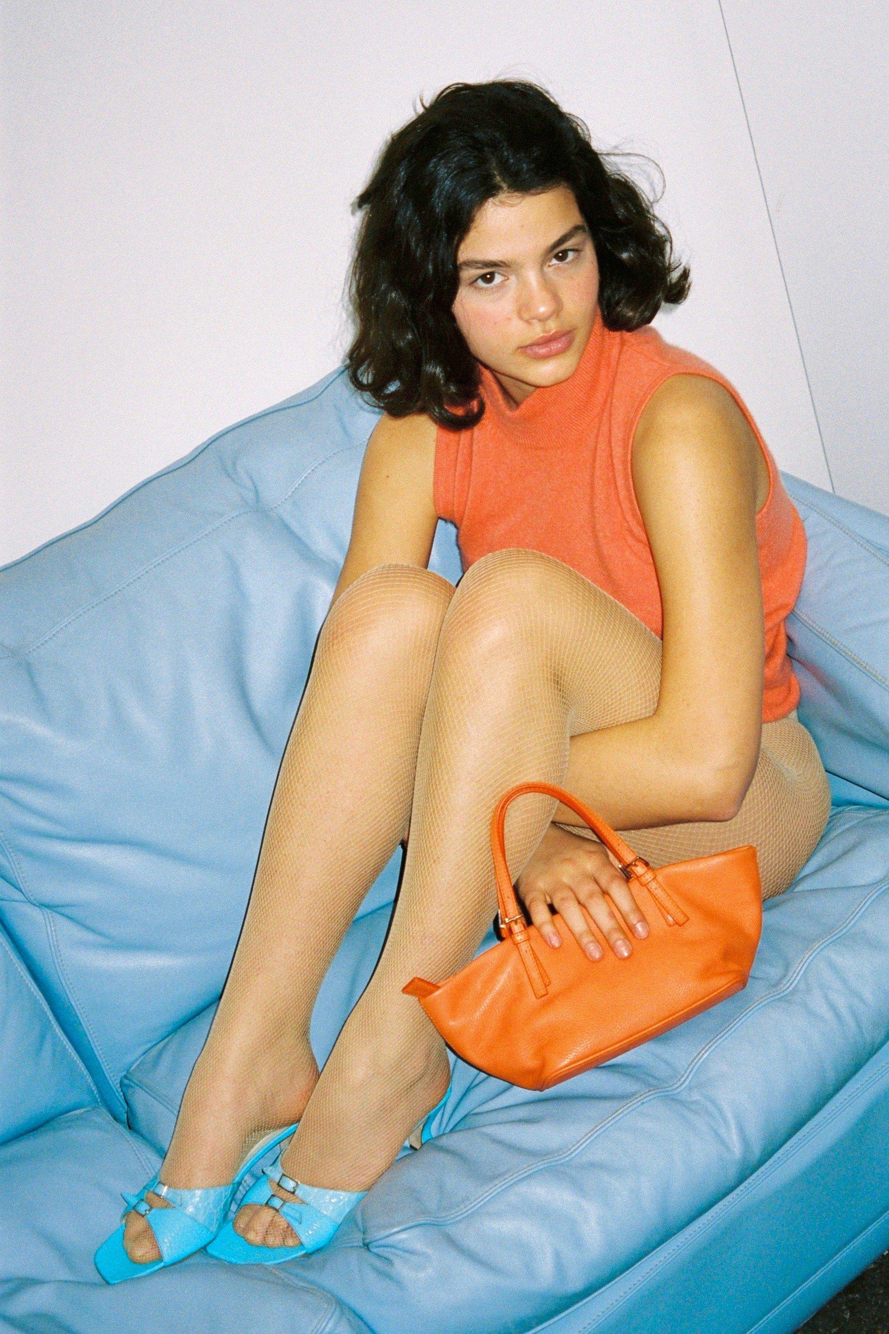Girl in orange sitting on a blue sofa