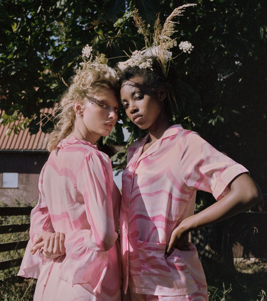 Two women wearing pink leaning on eachother