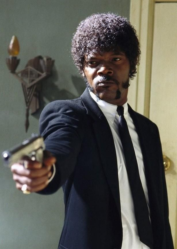 A man in a suit holding a gun