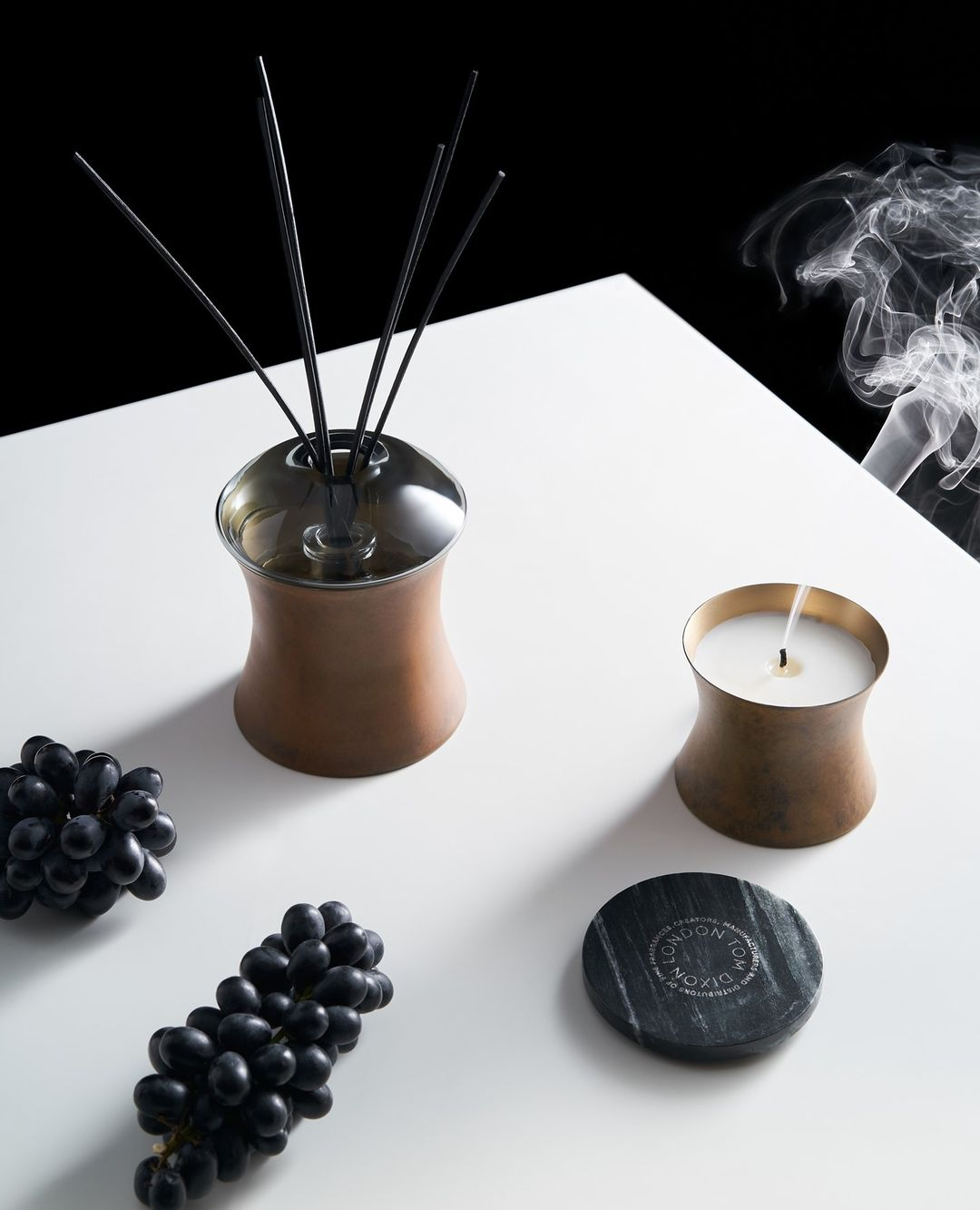 A Tom Dixon lit candle and diffuser