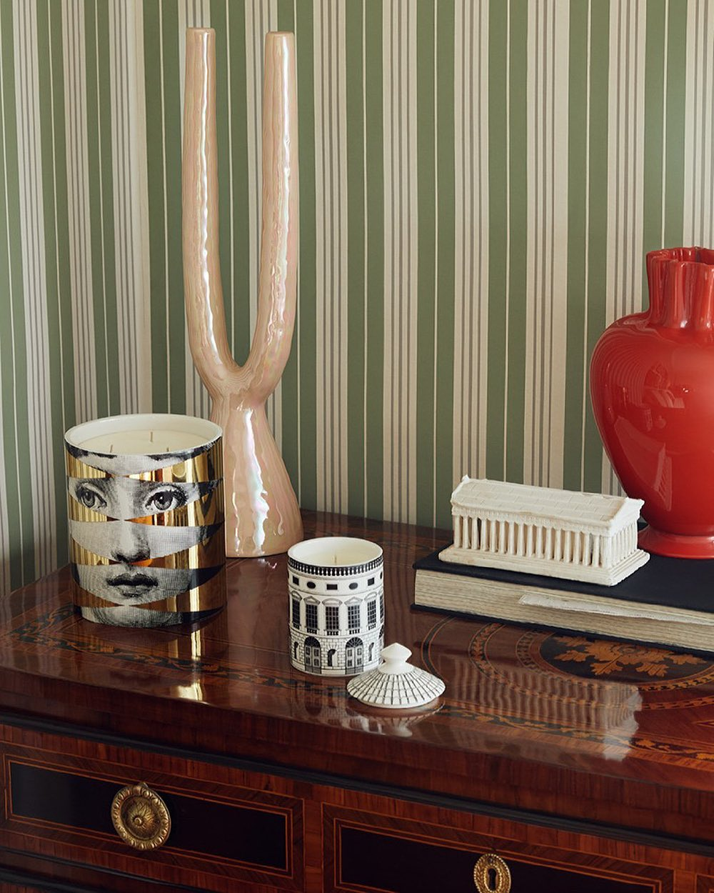 Two fornasetti candles on a a wooden dresser