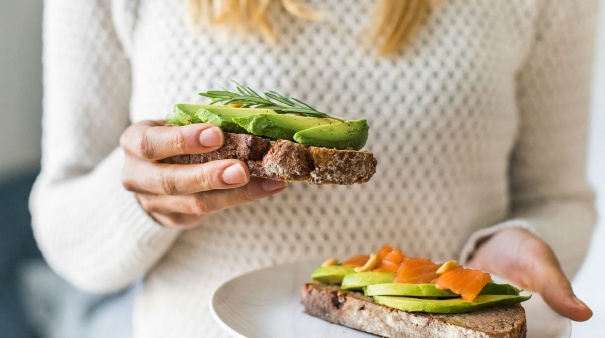 woman eating salmon and avocado for glowing skin
