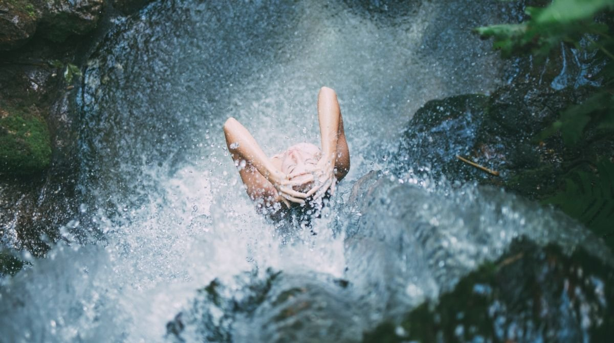 woman standing in a waterfall, with water running over her skin