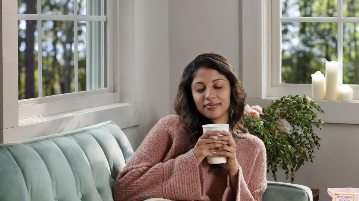 Woman closing her eyes on the sofa whilst holding a warm, soothing drink