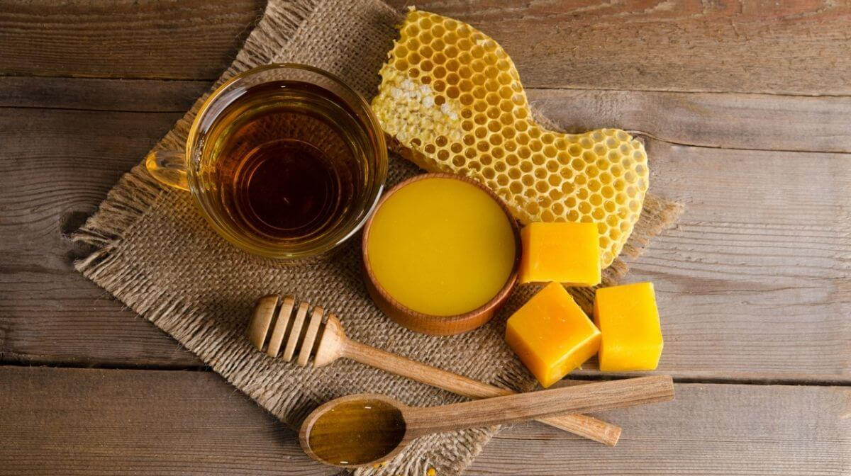 A cup of honey, blocks of beeswax and a honeycomb on a wooden table