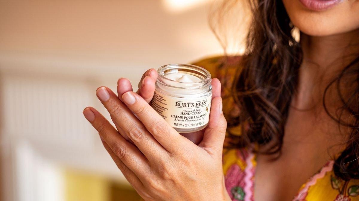 Jasmine Hemsley holding a pot of Burt's Bees Almond & Milk Hand Cream