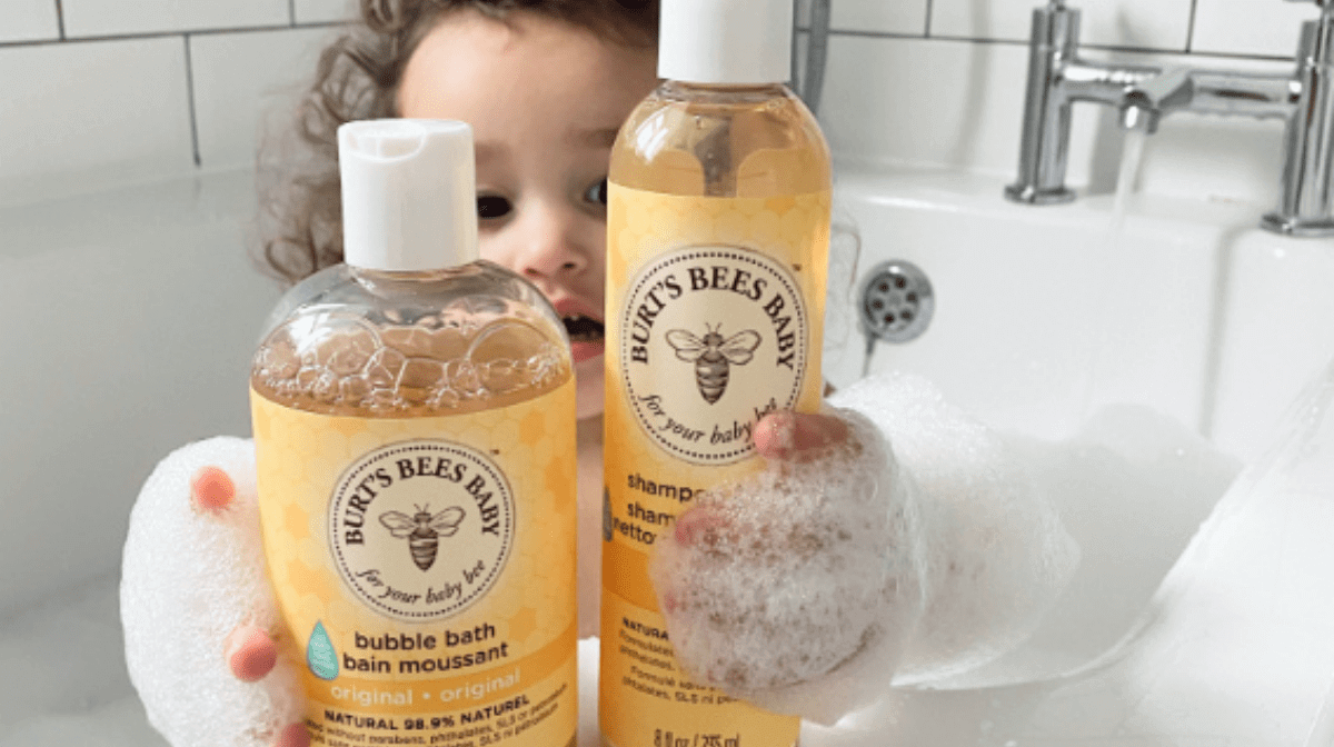 A baby in a bath holding up a bottle of Burt's Bees Baby Bubble Bath & Burt's Bees Baby Shampoo and Body Wash