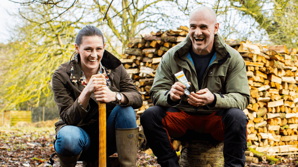 Ed Stafford and Laura Bingham sat outside on a pile of wood using the Burt's Bees Res-Q Cream