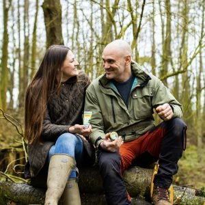 Ed Stafford and Laura Bingham sat outside on tree stumps holding Burt's Bees Res-Q Cream & Balm