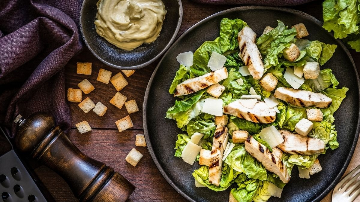 chicken caesar salad on a black plate