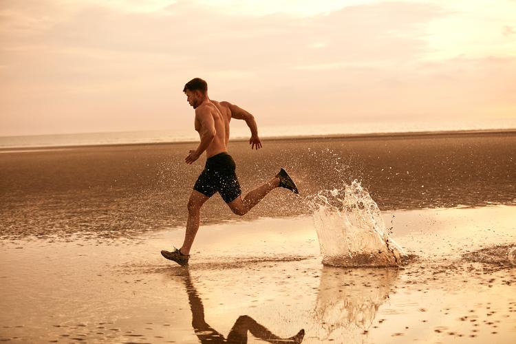Muž běžící po pláži