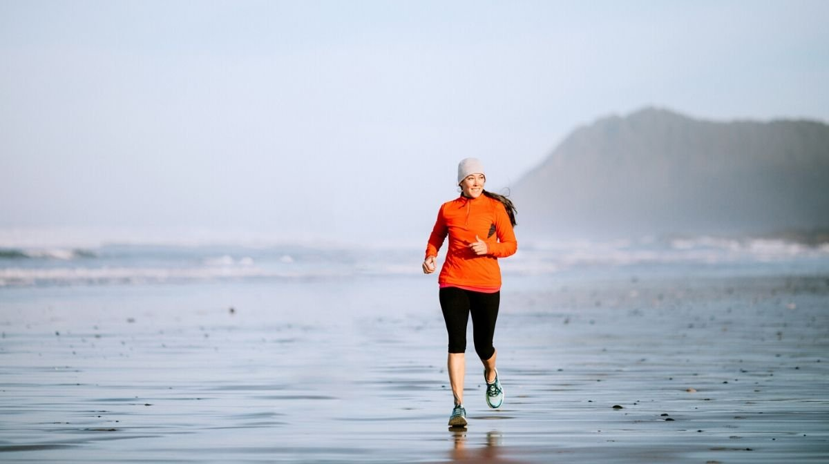 woman running along the beach to support a healthy lifestyle