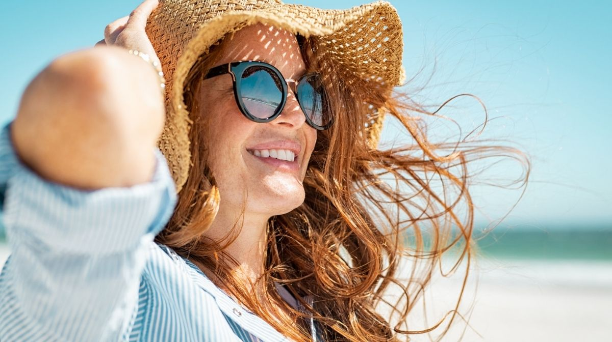 woman protecting her eyes from the sun with a hat and sunglasses