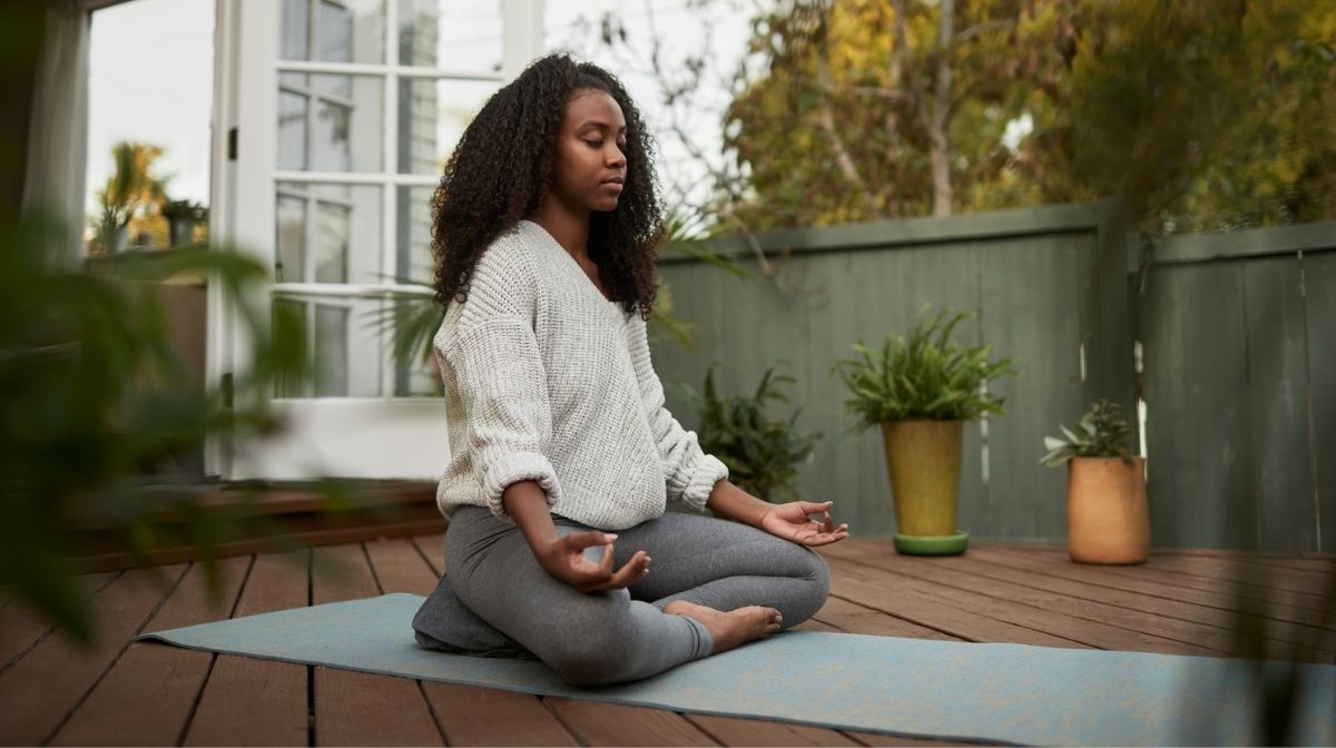 Woman sat in the lotus pose outside on her patio.