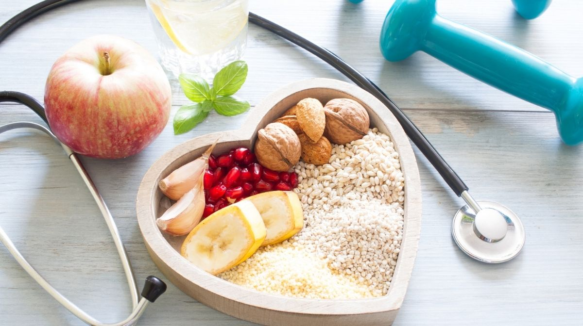 Birdseye view of heart shaped bowl containing heart healthy foods, next too dumbbells and a stethoscope.
