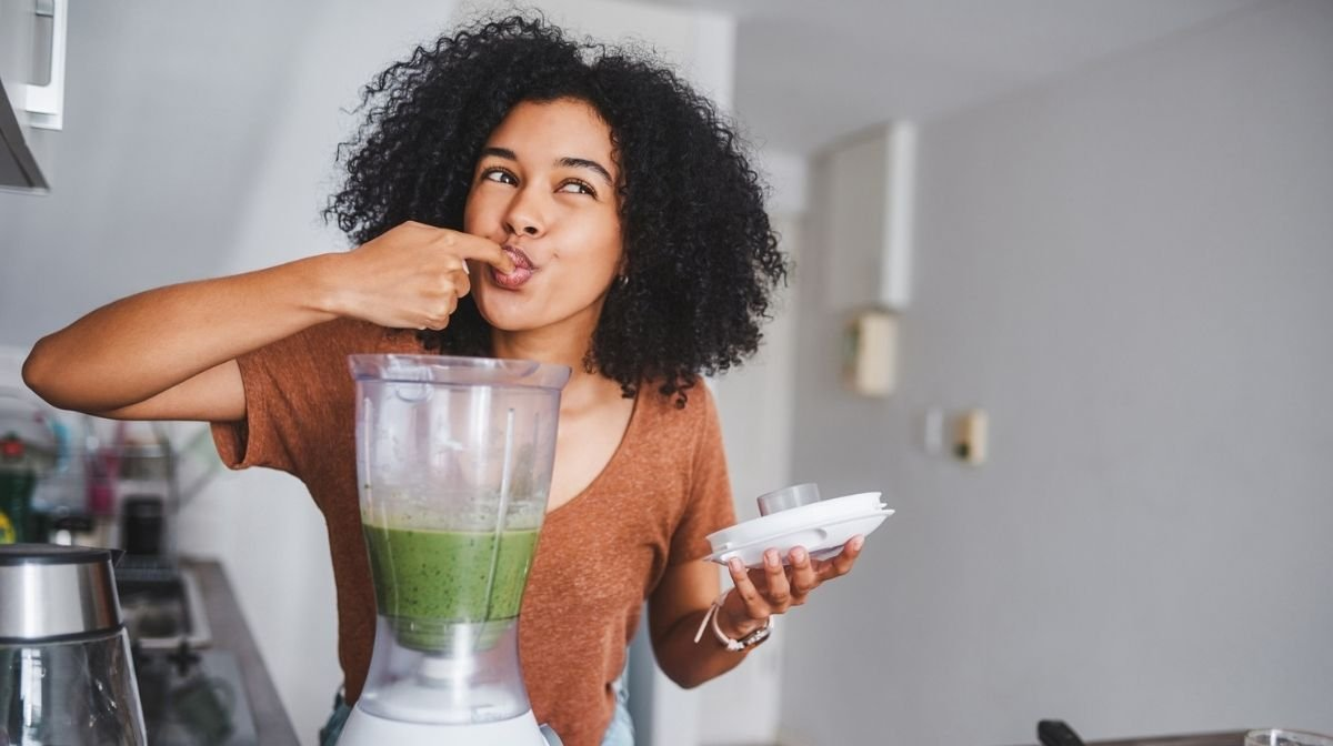 Woman making and trying a green smoothie.