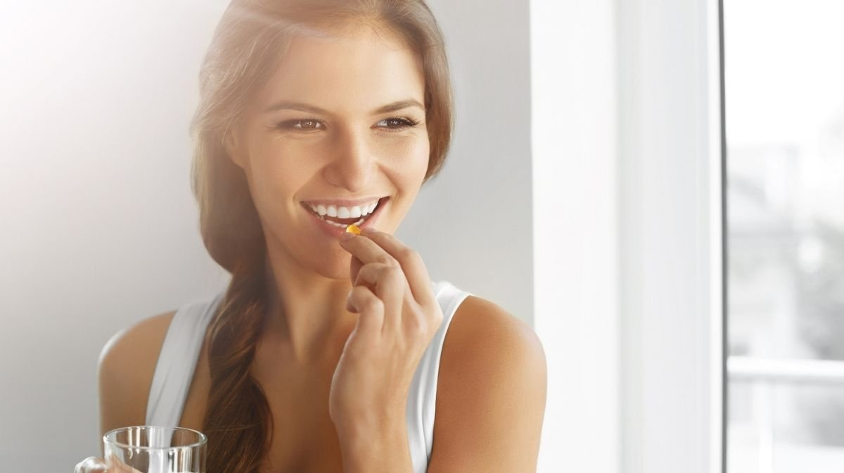 Woman taking an omega-3 supplement softgel.