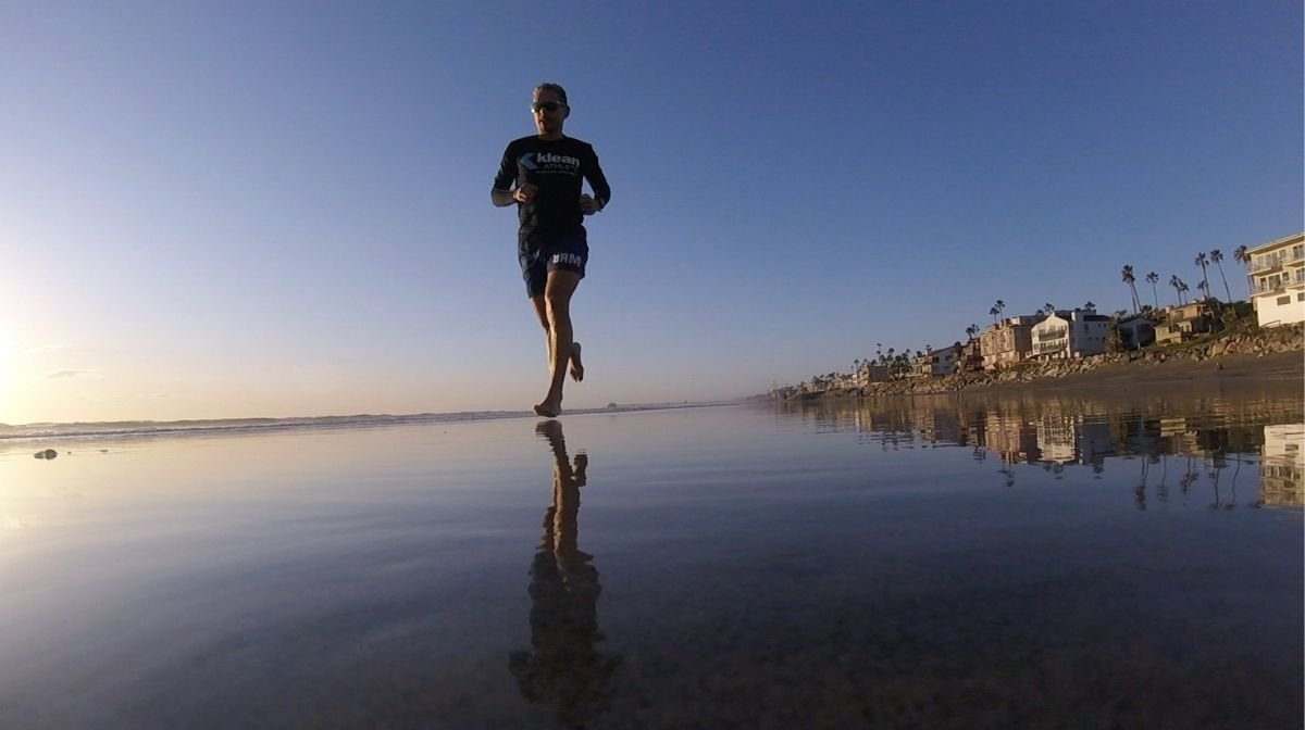Sponsored Klean Athlete Kevin Portmann running at sunset on the beach