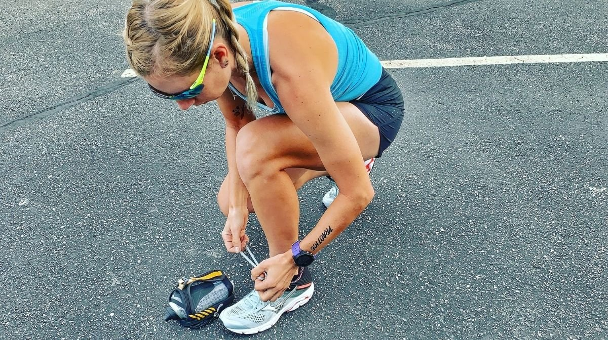 Klean Team Athlete tying her shoelace whilst out for a run.