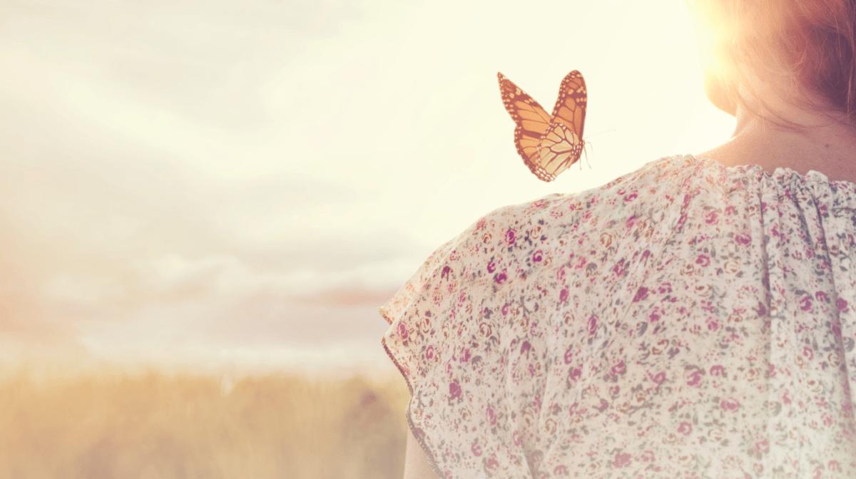 Image d'un papillon au-dessus de l'épaule d'une femme au coucher du soleil, pour accompagner un article sur l'importance de trouver les bons soins pour les peaux sensibles