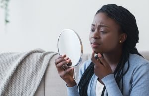 African Girl Looking In Round Mirror and Touching Her Chin