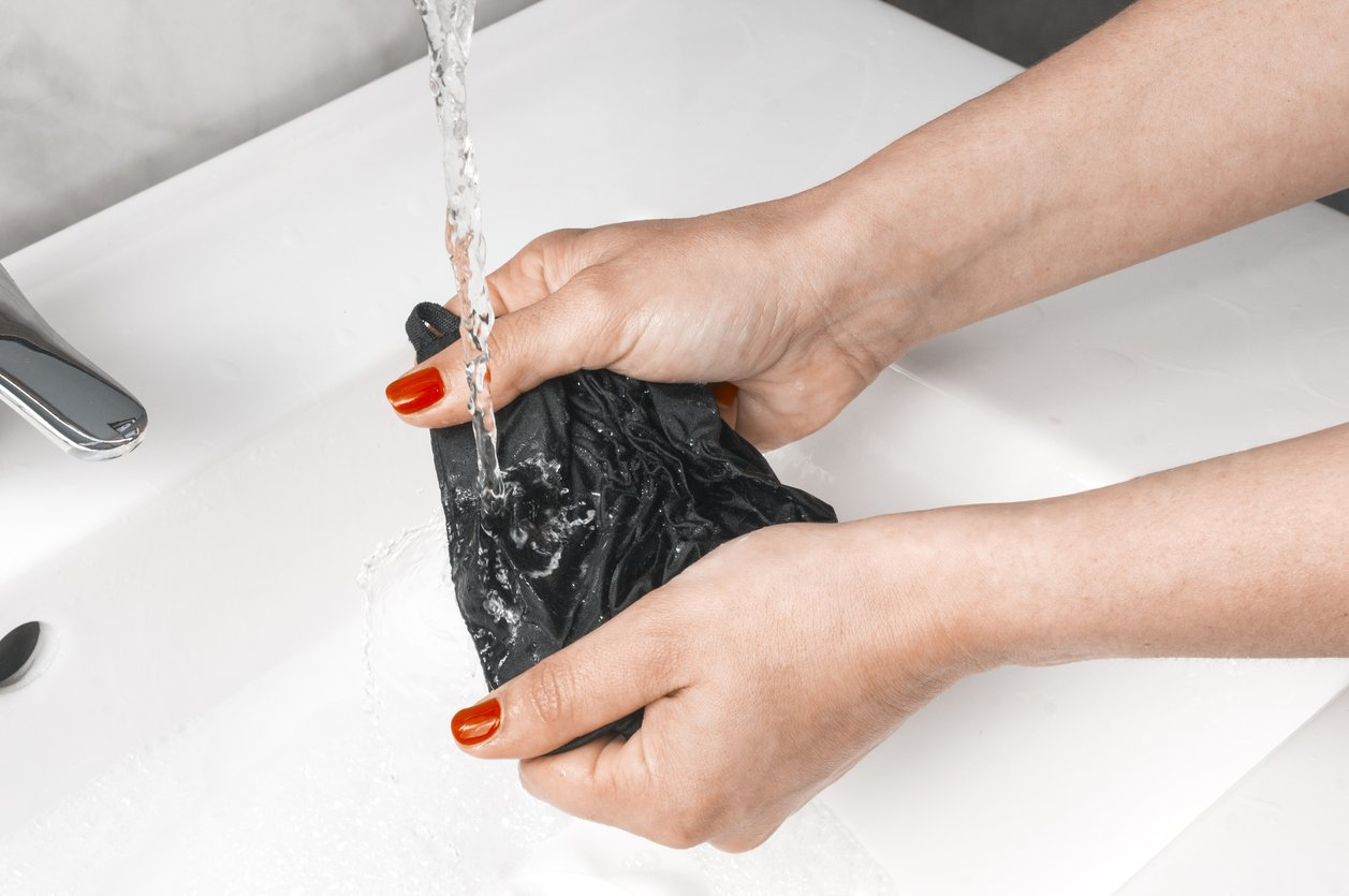 Woman rinse a black fabric protective mask under running water in the bathroom sink