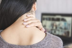 woman having neck pain while working on computer laptop