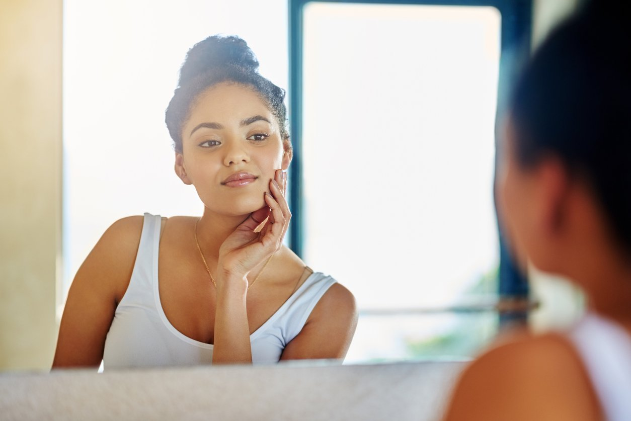 women looking into a mirror examing her skin