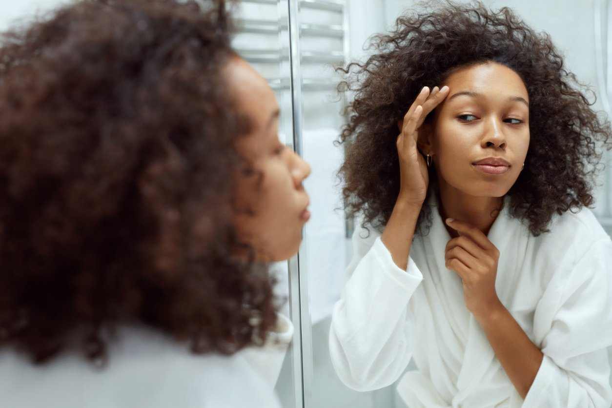 Skin care. Woman touching face skin and looking at mirror at bathroom. Portrait of beautiful african girl with afro hair after shower going through her morning beauty routine