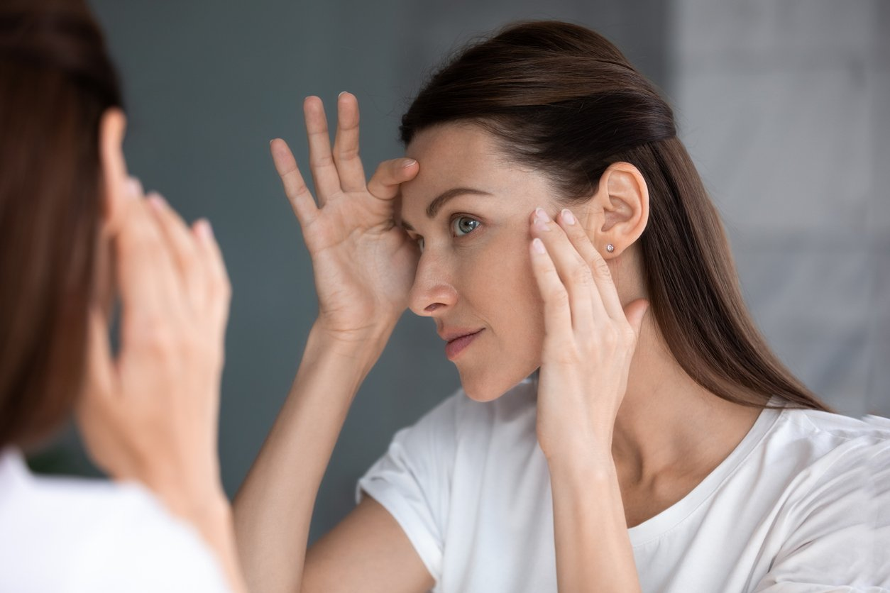 Women looking into the mirror with her hands on her face