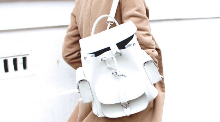 A woman wearing a white Grafea backpack.