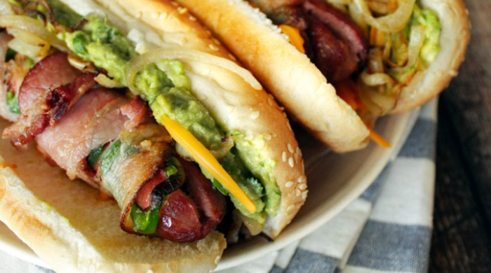 Hot dogs wrapped in bacon with guacamole.