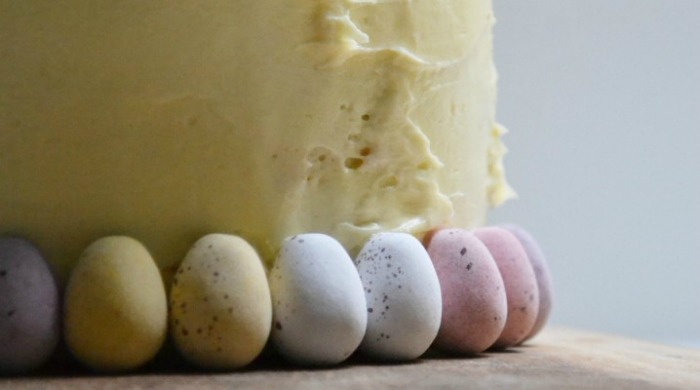 A cake being covered with Mini Eggs.