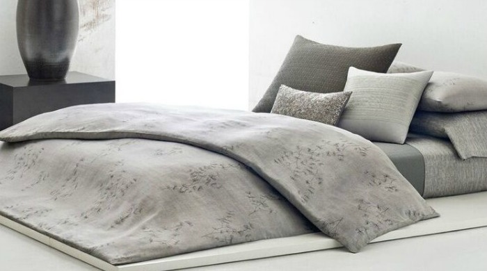 A bed made up with grey Calvin Klein Acacia bed linen.