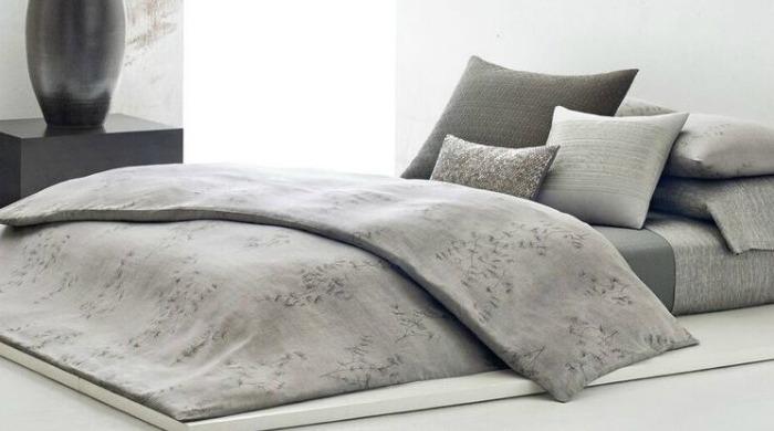 A bed made up with grey Calvin Klein Acacia bed linen.