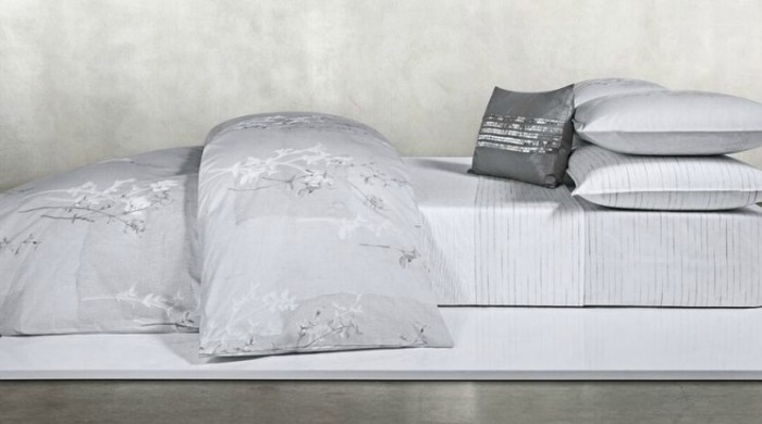 A bed made up with grey Calvin Klein Claytonia bed linen.