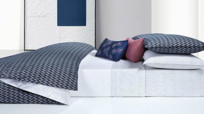 A bed made up with Calvin Klein Aurora Indigo bed linen.