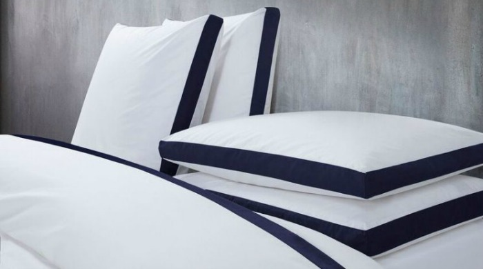 A bed made up with white Calvin Klein Canyon Indigo bed linen.