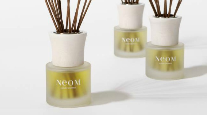 Three NEOM reed diffusers against a white background.
