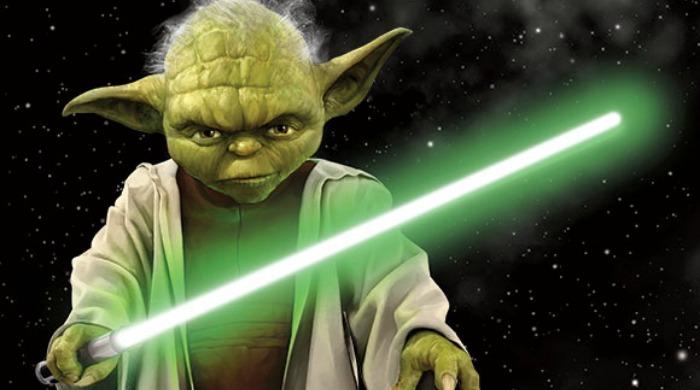 Yoda holding a green lightsaber.