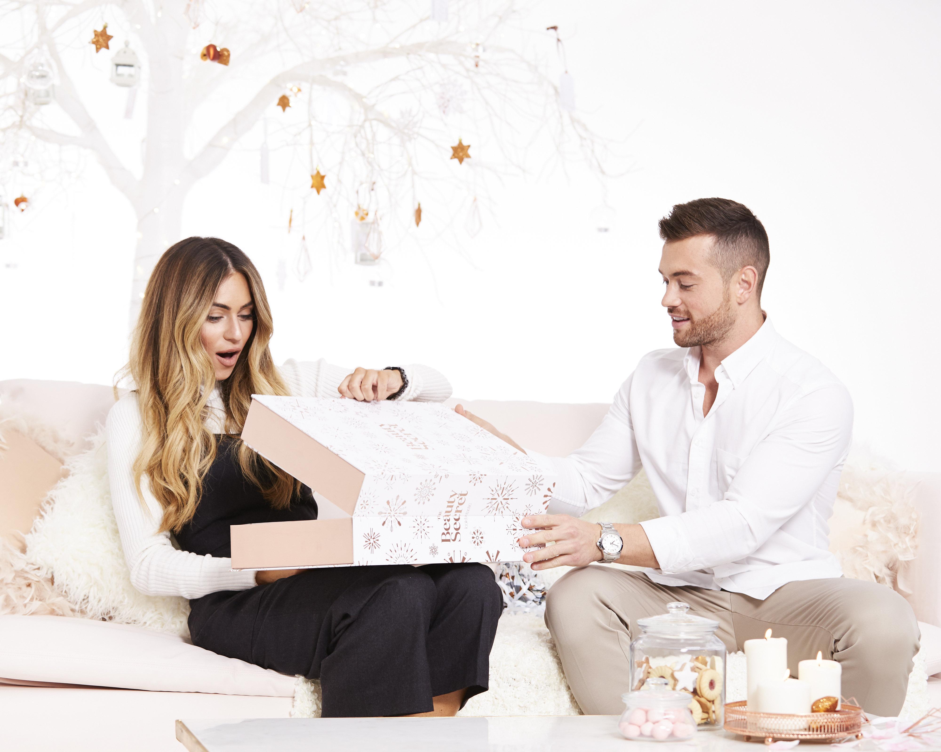 Una pareja abre nuestro calendario de adviento, sonriendo