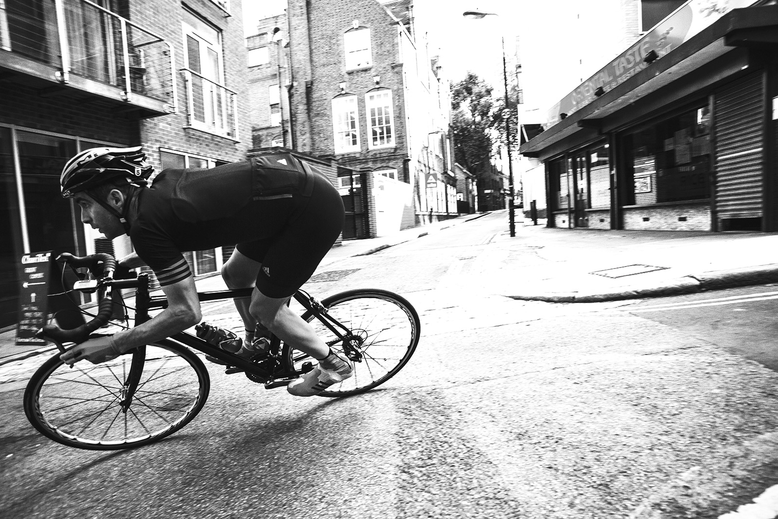 Cyclist riding round a bend wearing adidas cycling gear