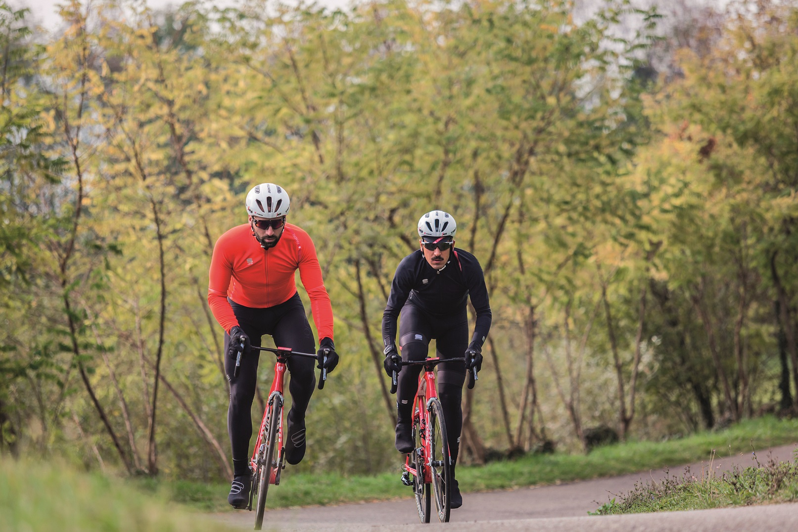 two cyclists riding their road bikes in winter