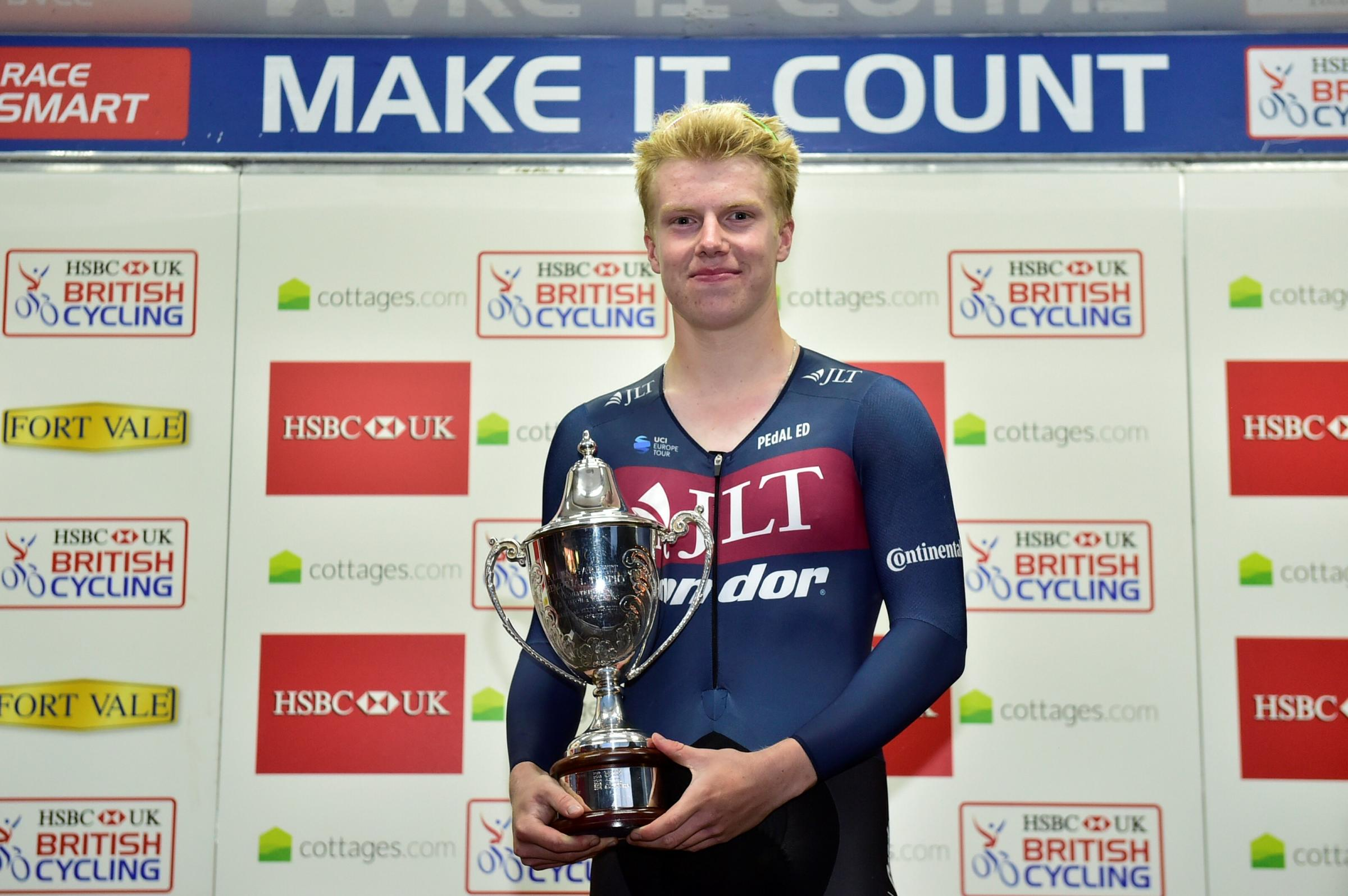 Matt Gibson on the podium with the elite criterium series winner trophy.
