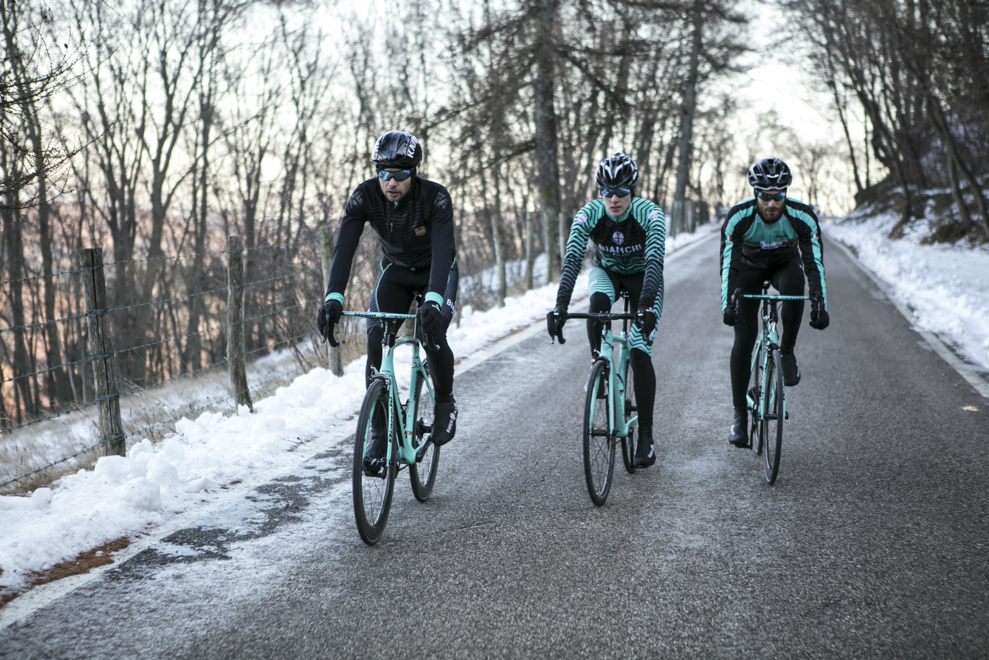 Three cyclists training together in the snow in Bianchi clothing.