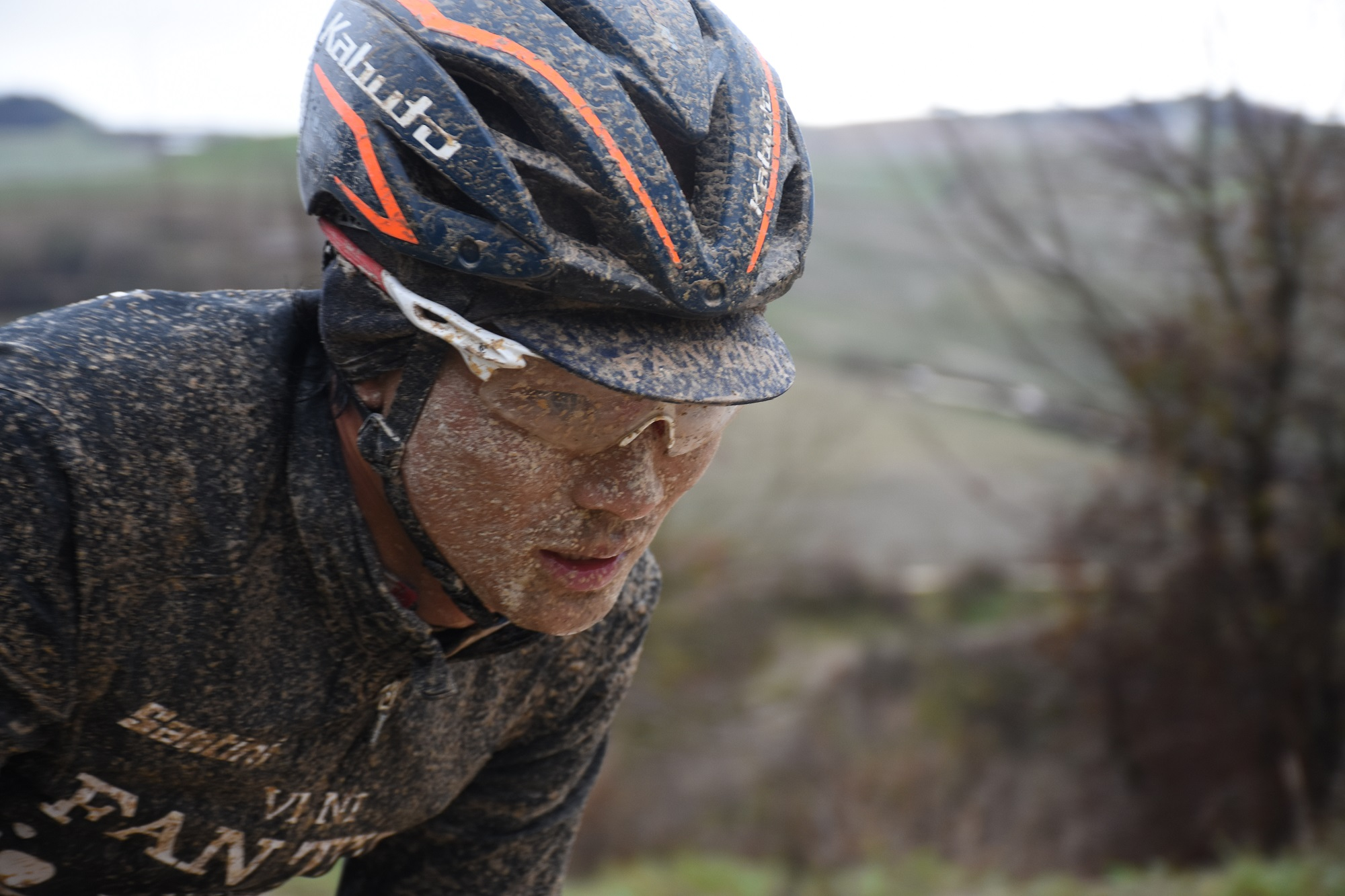 a mud-splattered rider on the dirt roads in the strade bianche 2018