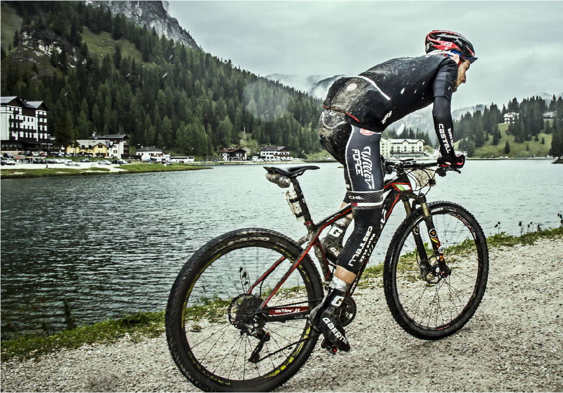 a mountain biker with a dirty bike that is need of some mountain bike maintenance
