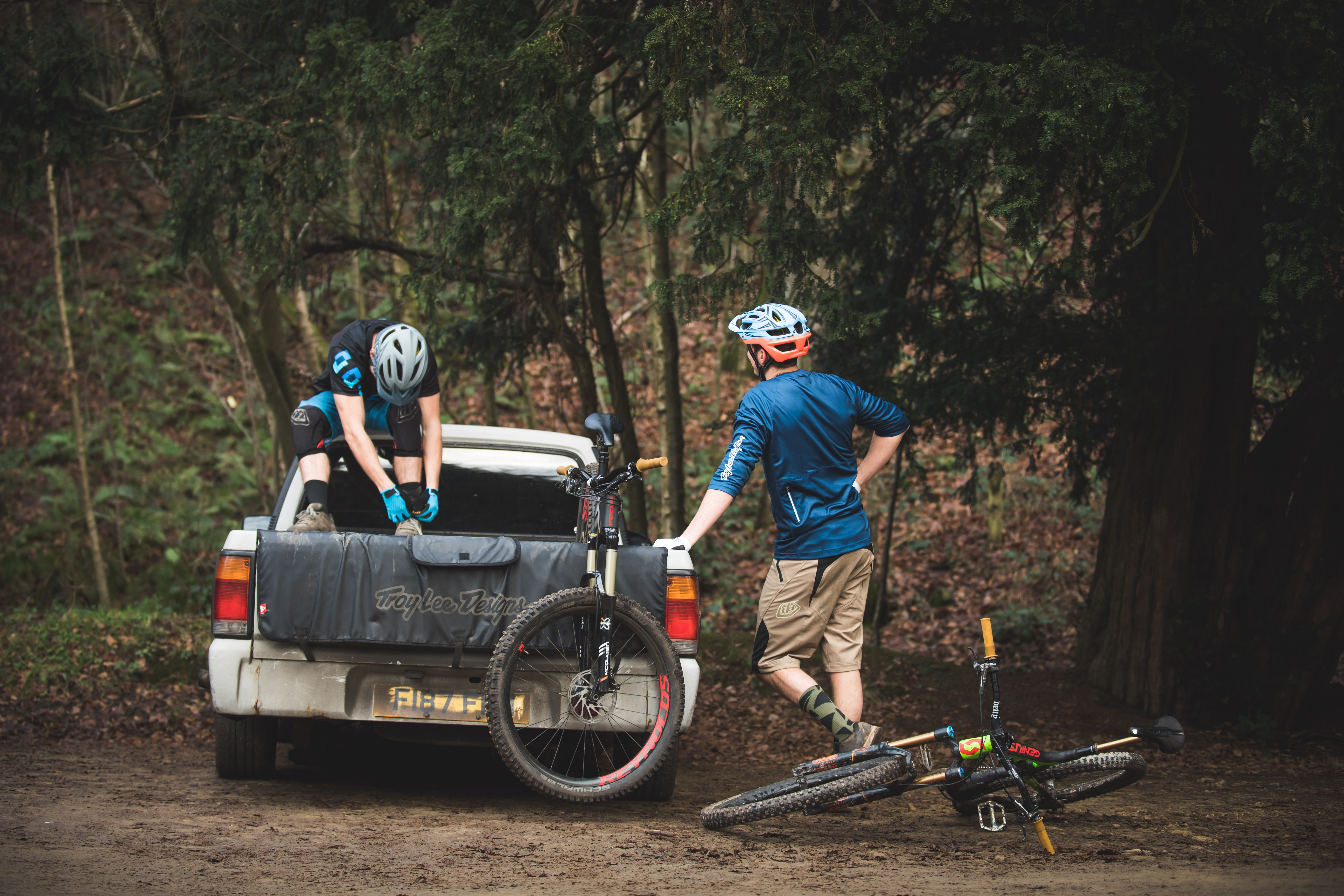 two mountain bikers and their mountain bikes getting ready for a ride next to a car